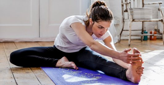 Young woman practicing yoga, touching toes in apartment